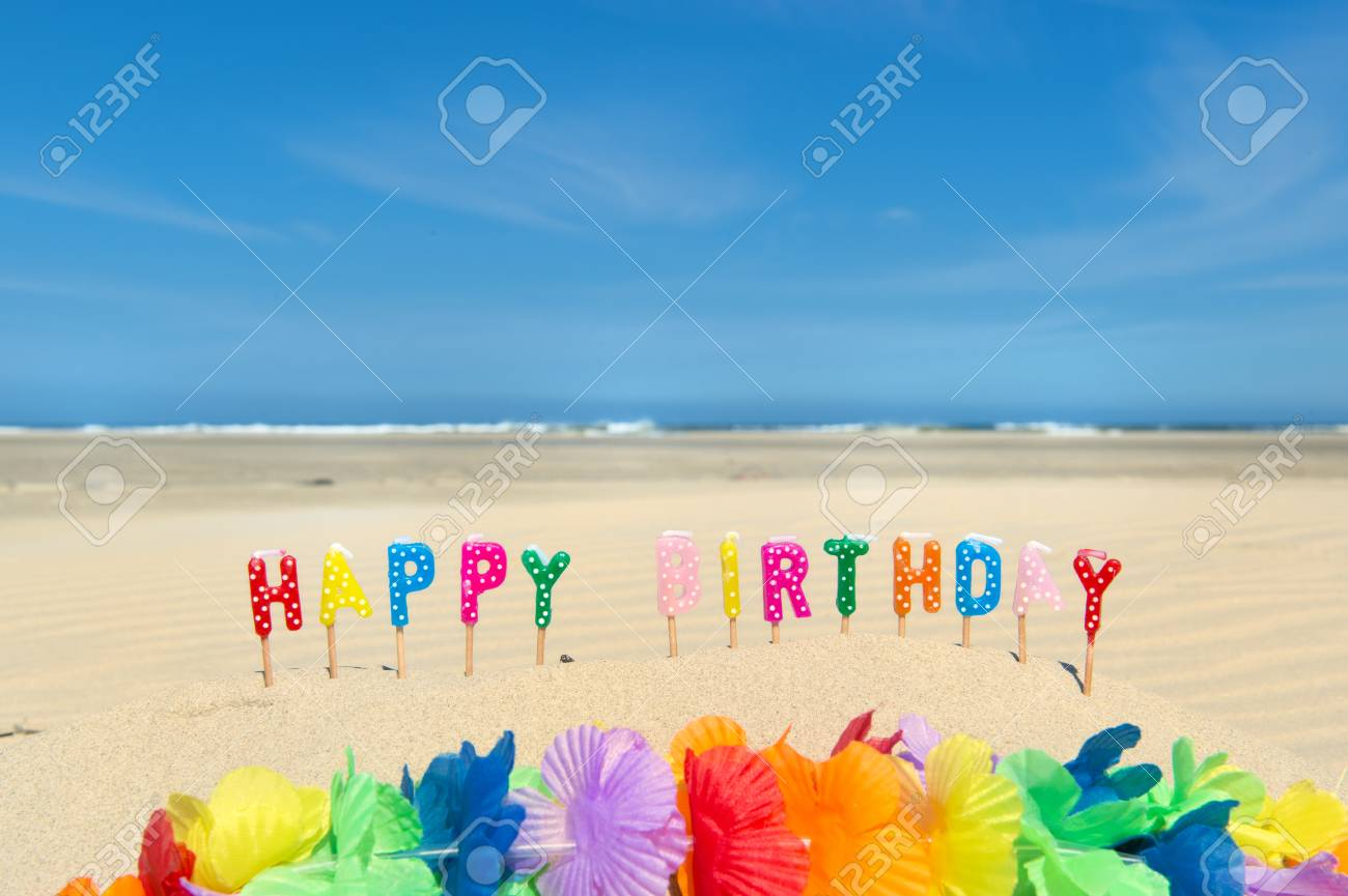 Happy Birthday Candles And Flower Garland At The Beach Stock Photo