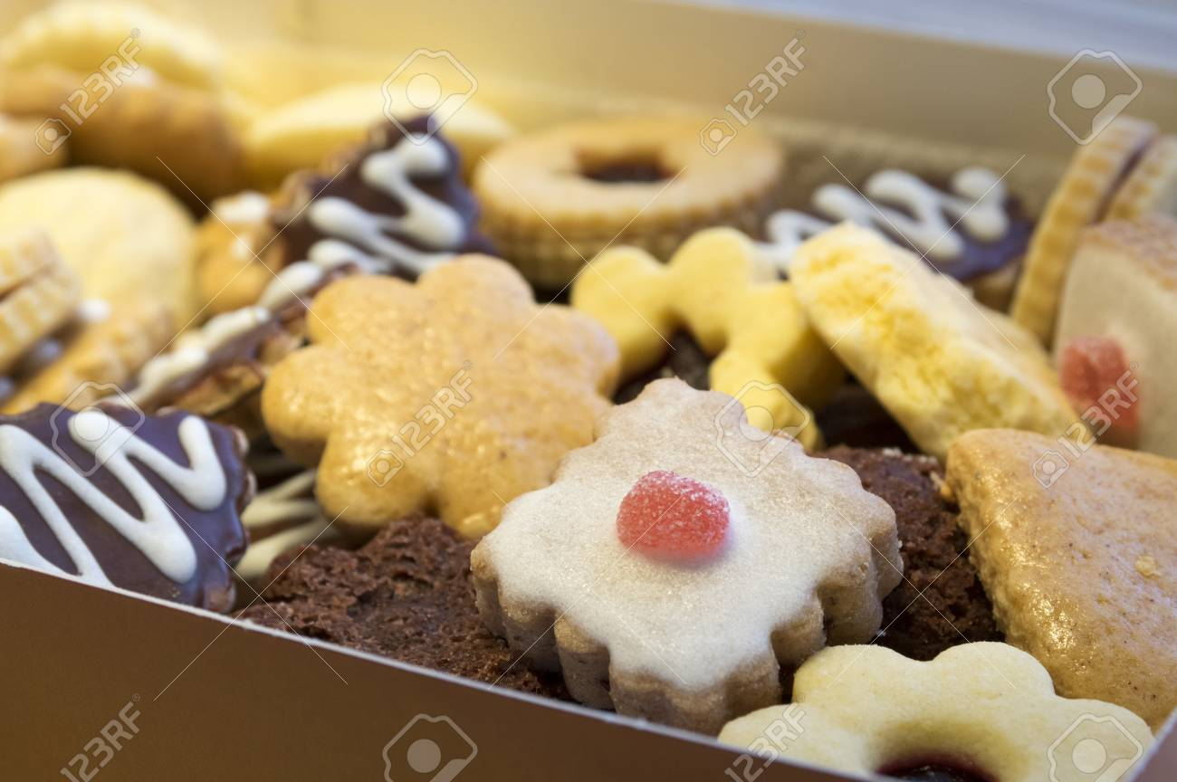Many Kinds Of Christmas Cookies In One Pile In The Brown Cardboard