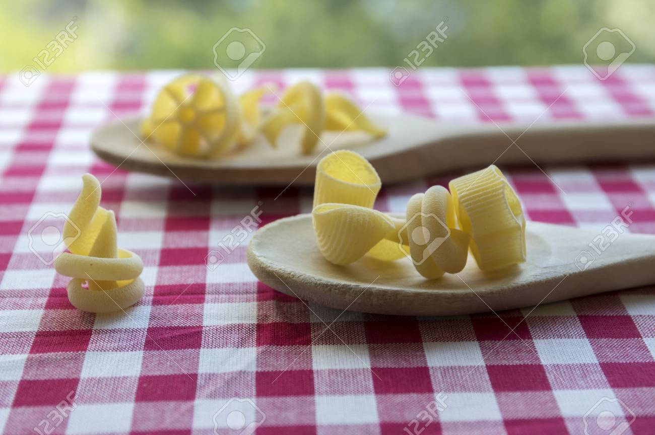 Stock Photo   Various Mix Of Pasta On Wooden Spoons On Purple White  Checkered Tablecloth, Shapes Ruotes And Macaroni
