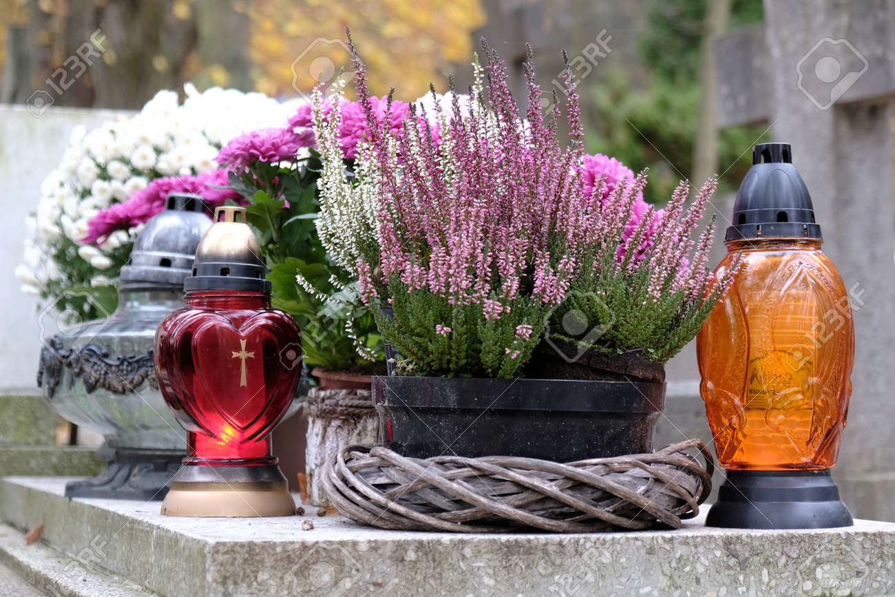 Colorful glass candles between autumn flowers in flower pots on grave in cemetery on November day - 158648777