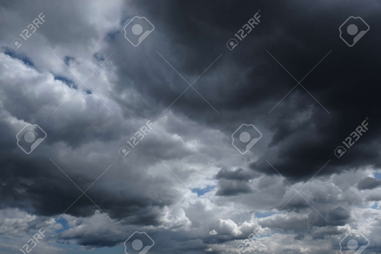 Dramatic sky with dark clouds lit by sun - 168285611