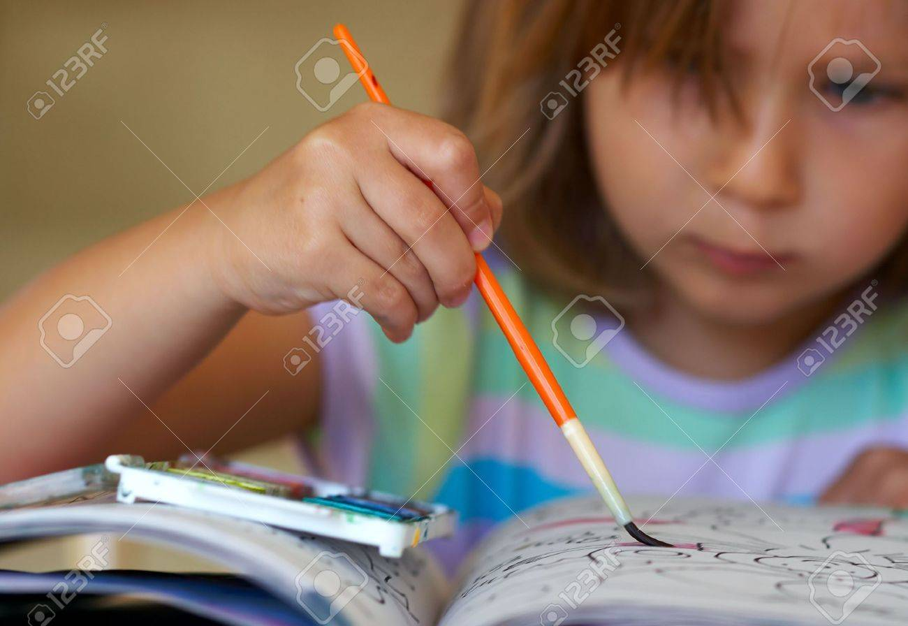 Girl coloring a book Stock Photo - 264921