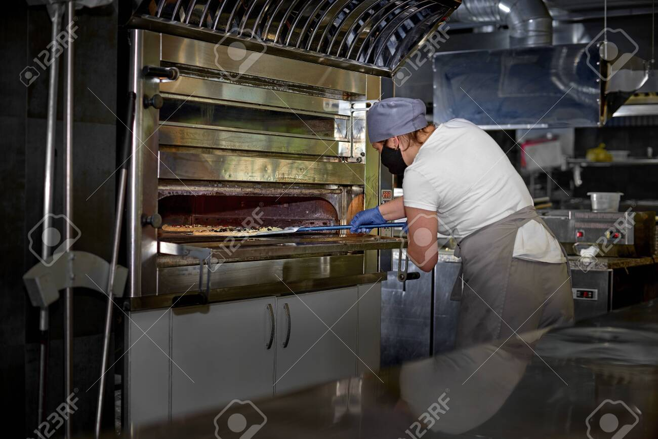 Restaurant professional open kitchen, Woman in a mask on her face, preparing pizza, new measures to fight the virus, cooking, profession and people concept - 149824500