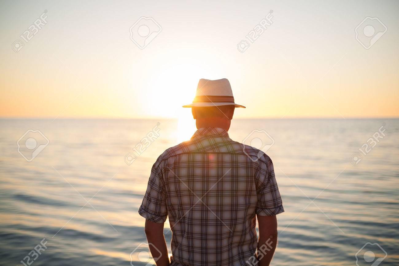 74600c4b7e Foto de archivo - Pie de iluminación de luz de fondo puesta de sol hombre  back view playa noche de verano