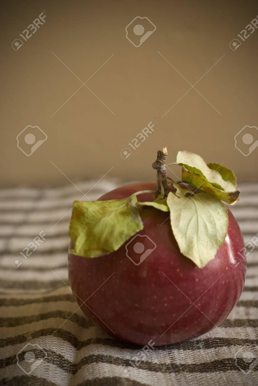 Une Pomme Rouge Avec Des Feuilles Vertes Sur Un Tapis Marron Et ...