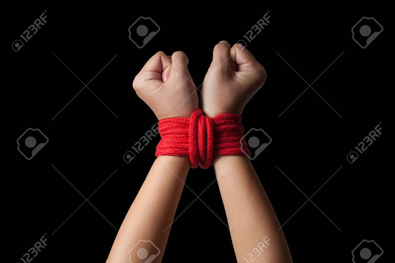 Hands of a missing kidnapped, abused, hostage, victim woman tied up with rope in emotional stress and pain, afraid, restricted, trapped, call for help, struggle, terrified. - 55539324