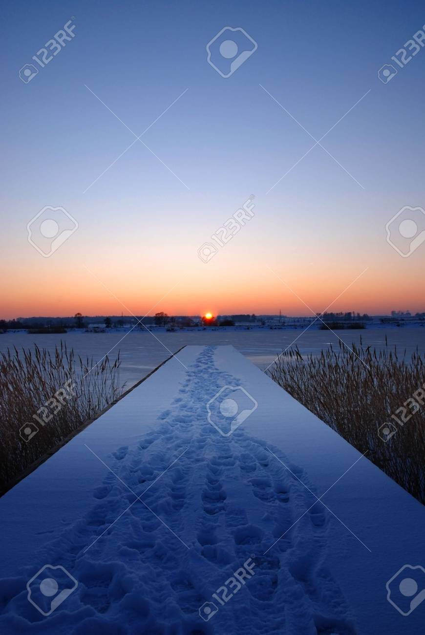 A pier by a frozen lake at sunset Stock Photo - 787238