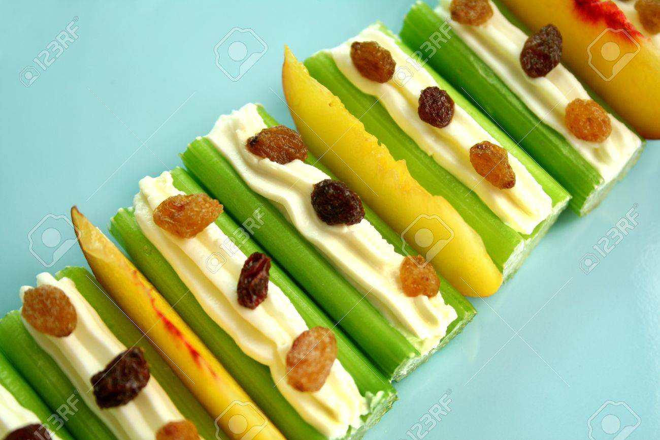 Healthy afternoon snack of celery sticks with cream cheese and sultanas. - 4315504