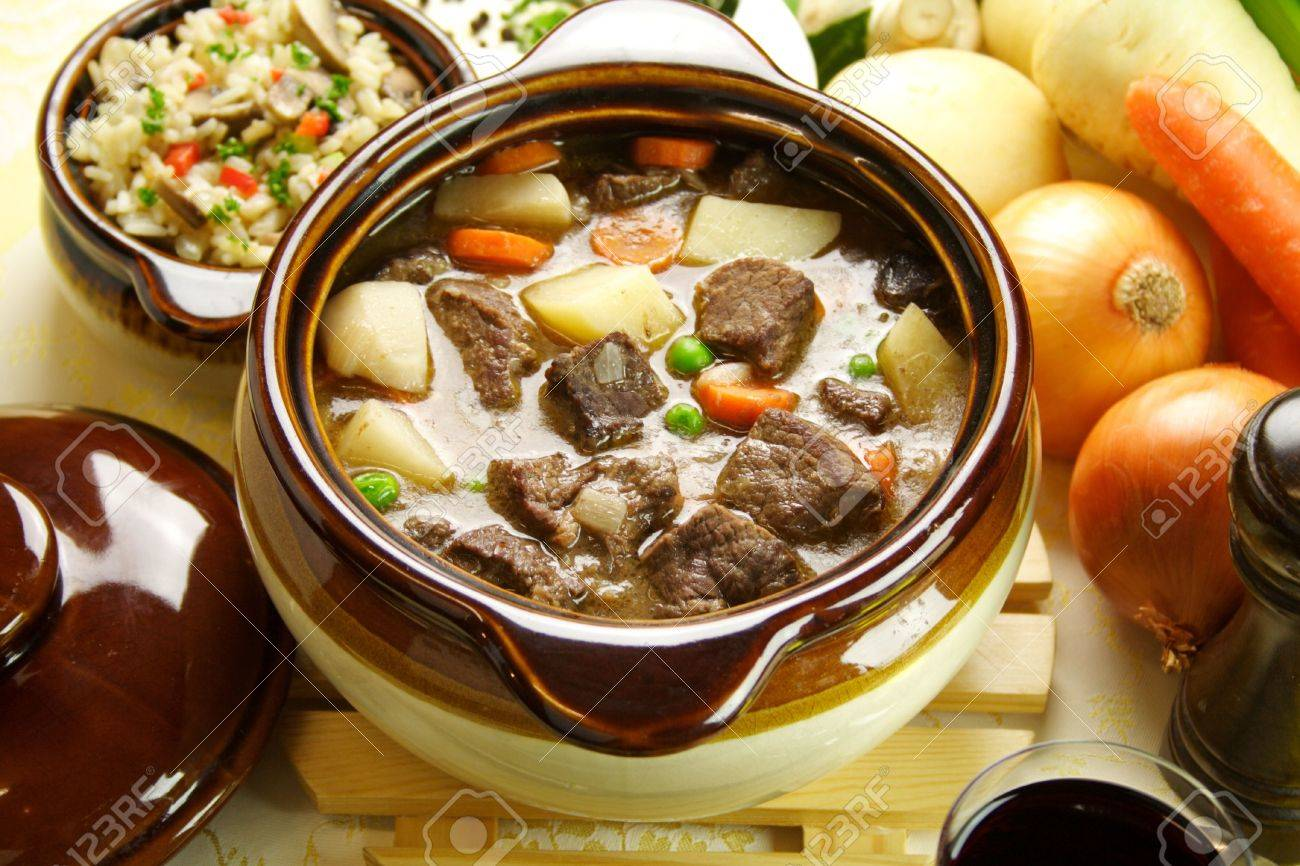 Table setting of freshly baked beef stew with savory rice and seasonal vegetables and herbs. - 4916197