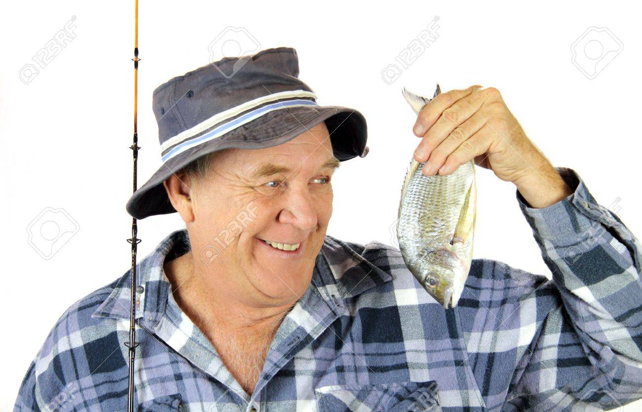 Proud middle aged fisherman holds up the fish he has just caught. Stock Photo - 5295034