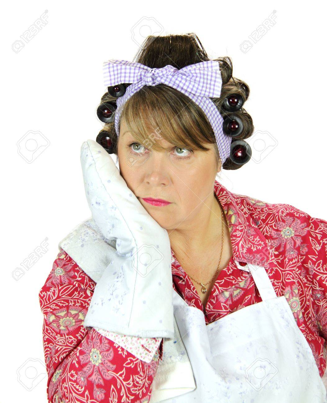 Terminally bored housewife leans on her oven mit dreaming of being somewhere else. Stock Photo - 5501205