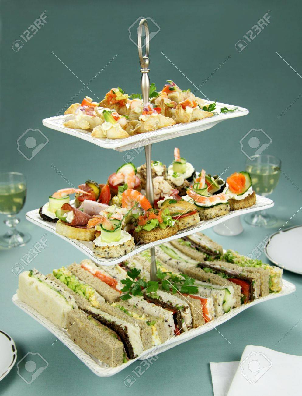 Delicious assorted finger food and sandwiches on a three tier stand. - 6490257