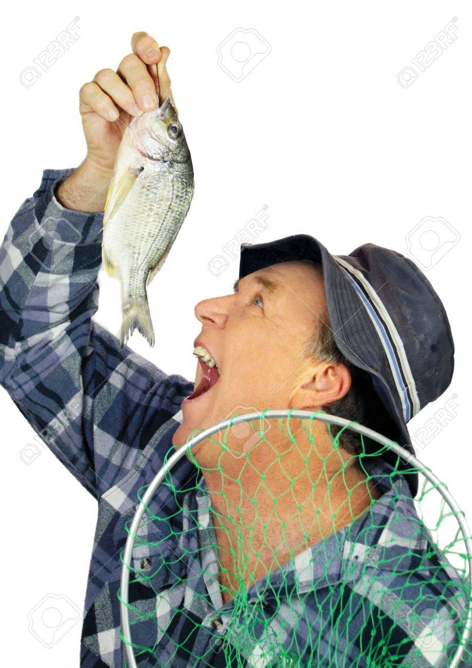 Middle aged fisherman pretends to drop a fresh raw fish into his mouth. Stock Photo - 7224630