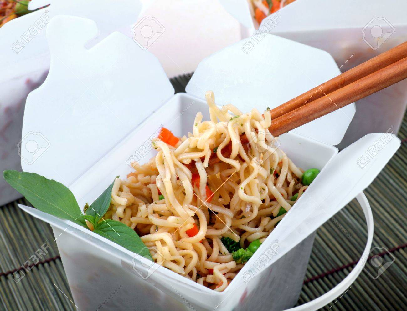 Take away egg noodles on chopsticks in a take away container. - 7732114