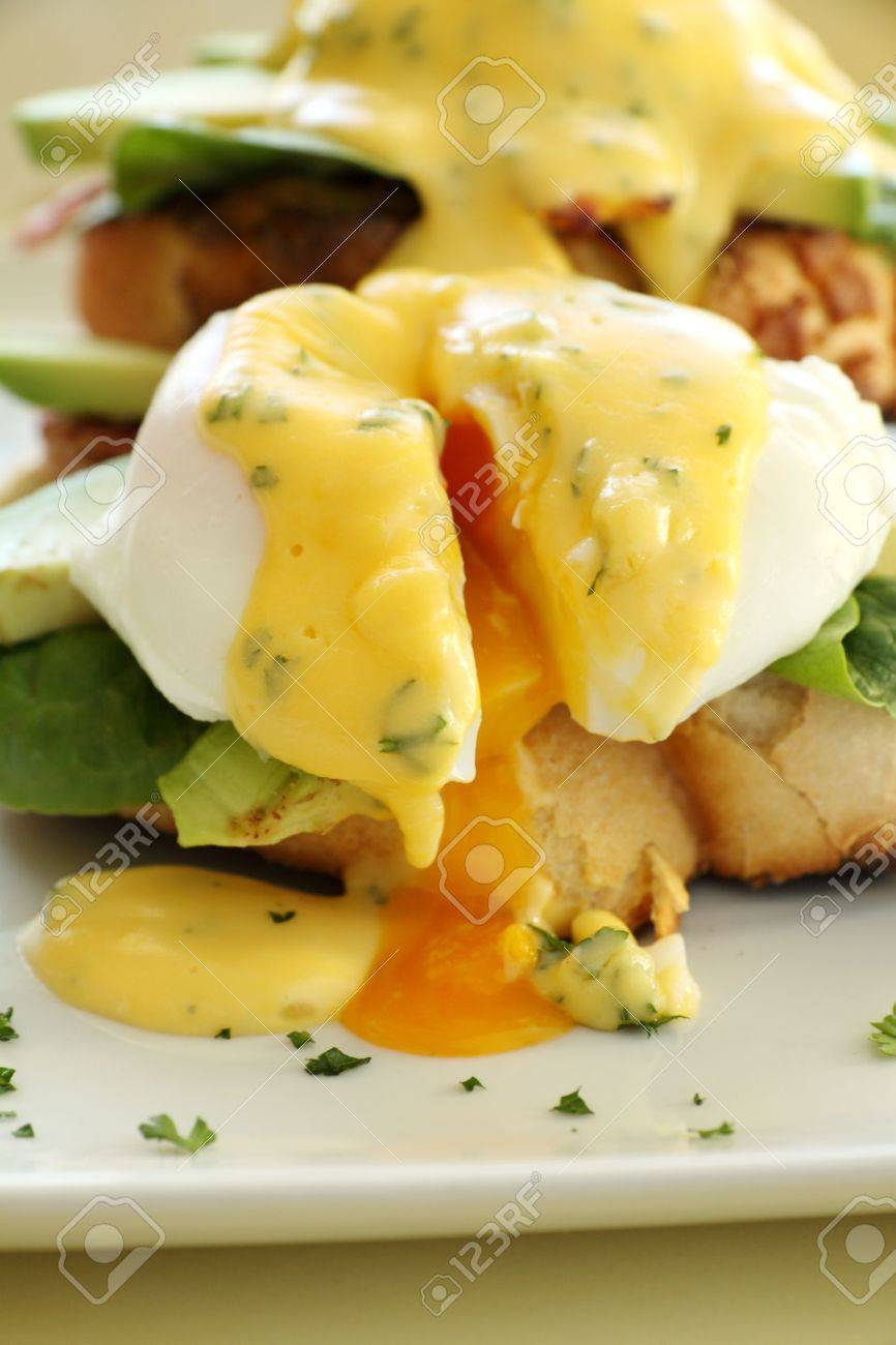Delicious eggs benedict with hollandaise sauce with avocado with egg yolk. - 10502609
