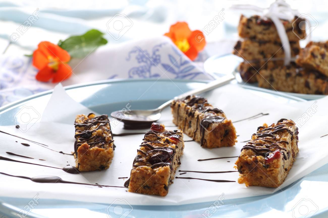 Fresh baked muesli bars with melted chocolate drizzled over the top. Stock Photo - 11070993