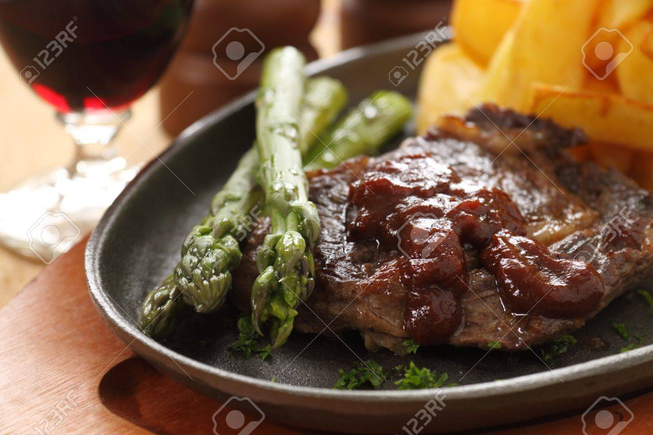 Grilled fillet steak with asparagus and barbeque sauce with potato wedges. - 11071000