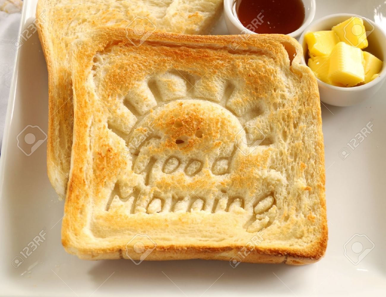 Slice of toast with Good Morning carved into it with butter and honey. - 12510093