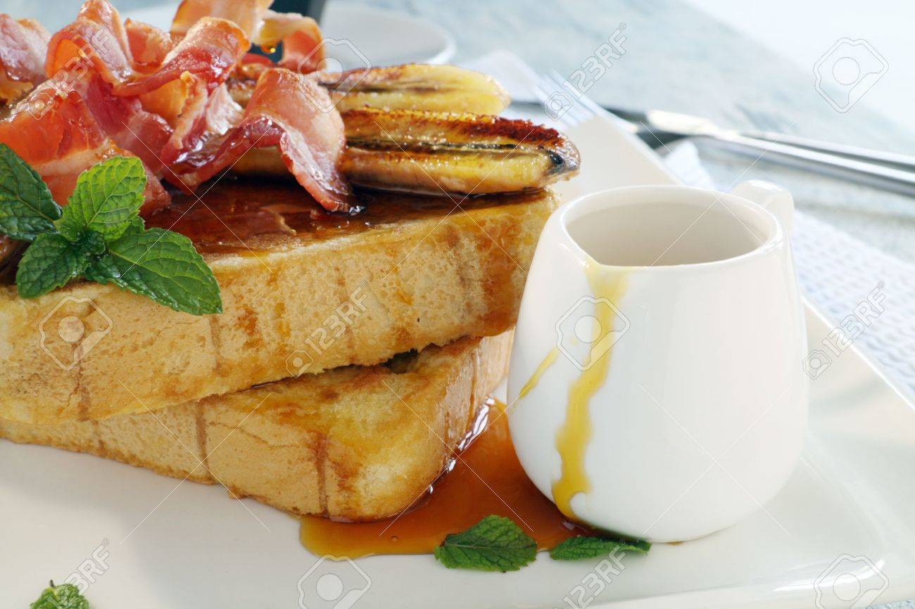 French toast with bacon and caramalized banana with maple syrup. - 13151638