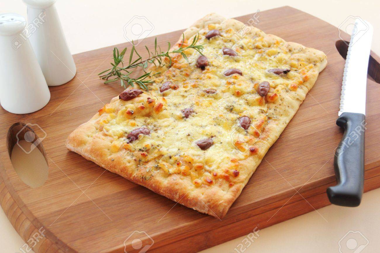 Rectangular gourmet pizza with cheese and olives ready to serve. - 15013673