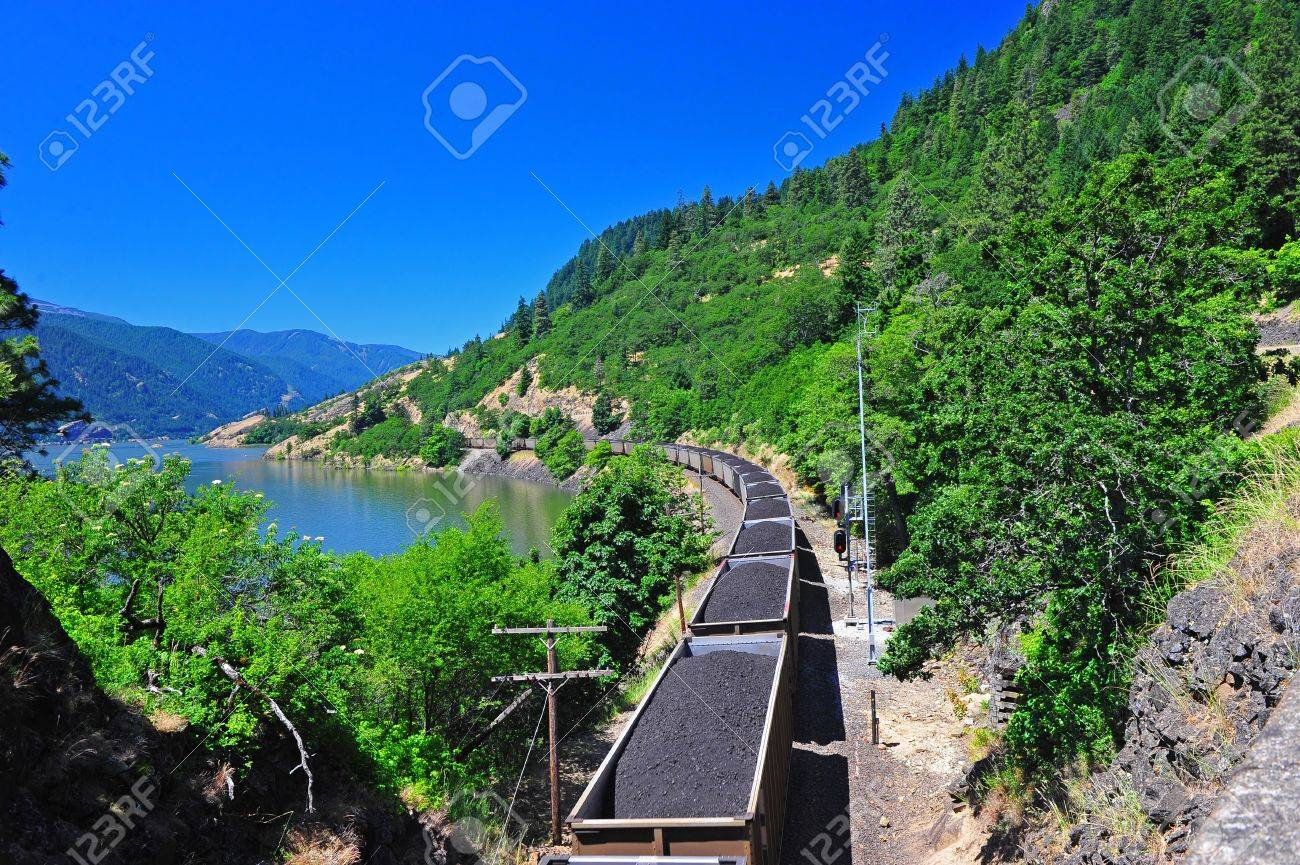 Train cars full of coal are being transported along the rail line through a scenic columbia river gorge. Stock Photo - 11646950