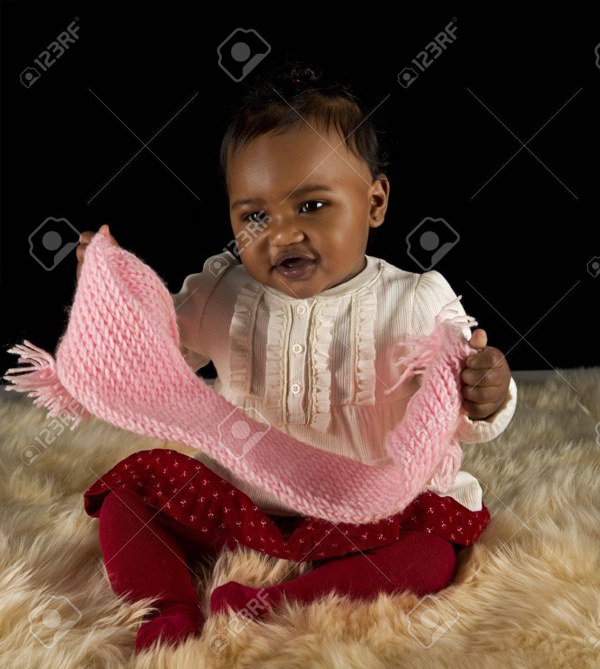beautiful baby girl playing with a pink scarf stock photo, picture