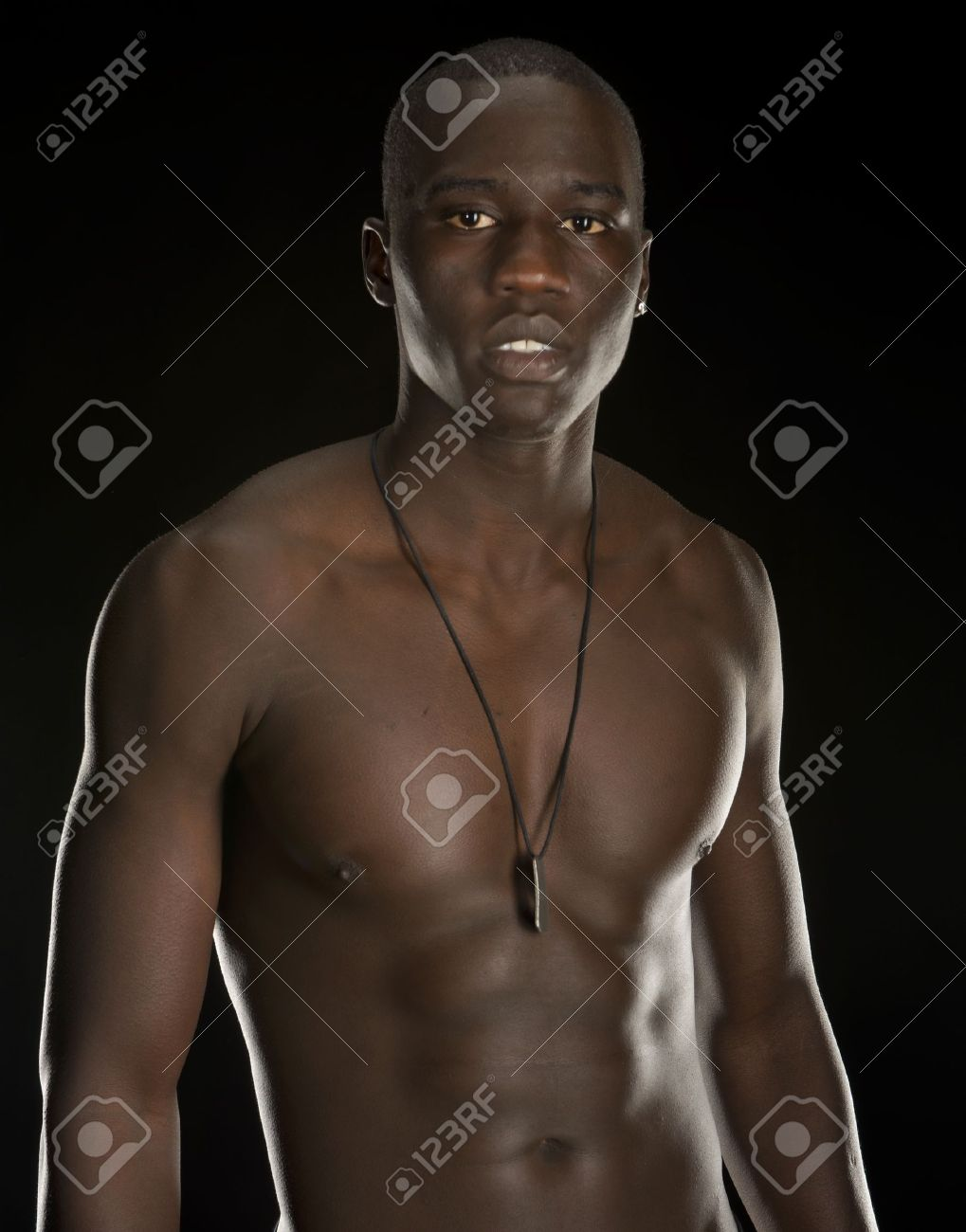 Bare chested young black male model isolated on a black background stock photo 16085409