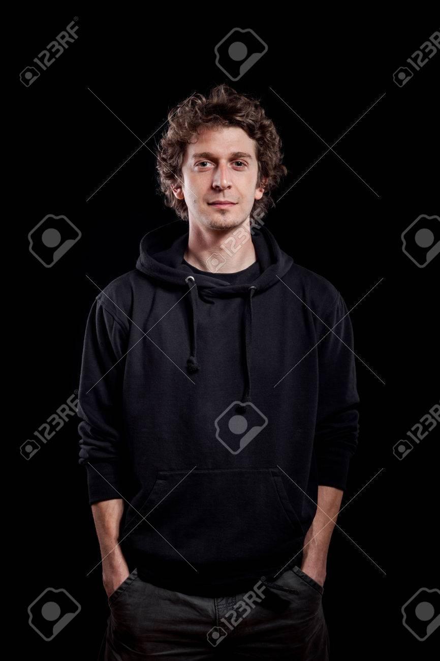 6f248ef45d17 Hombre joven pelo rizado caucásica vistiendo sudadera con capucha negro.  Retrato oscuro tomada en fondo negro.