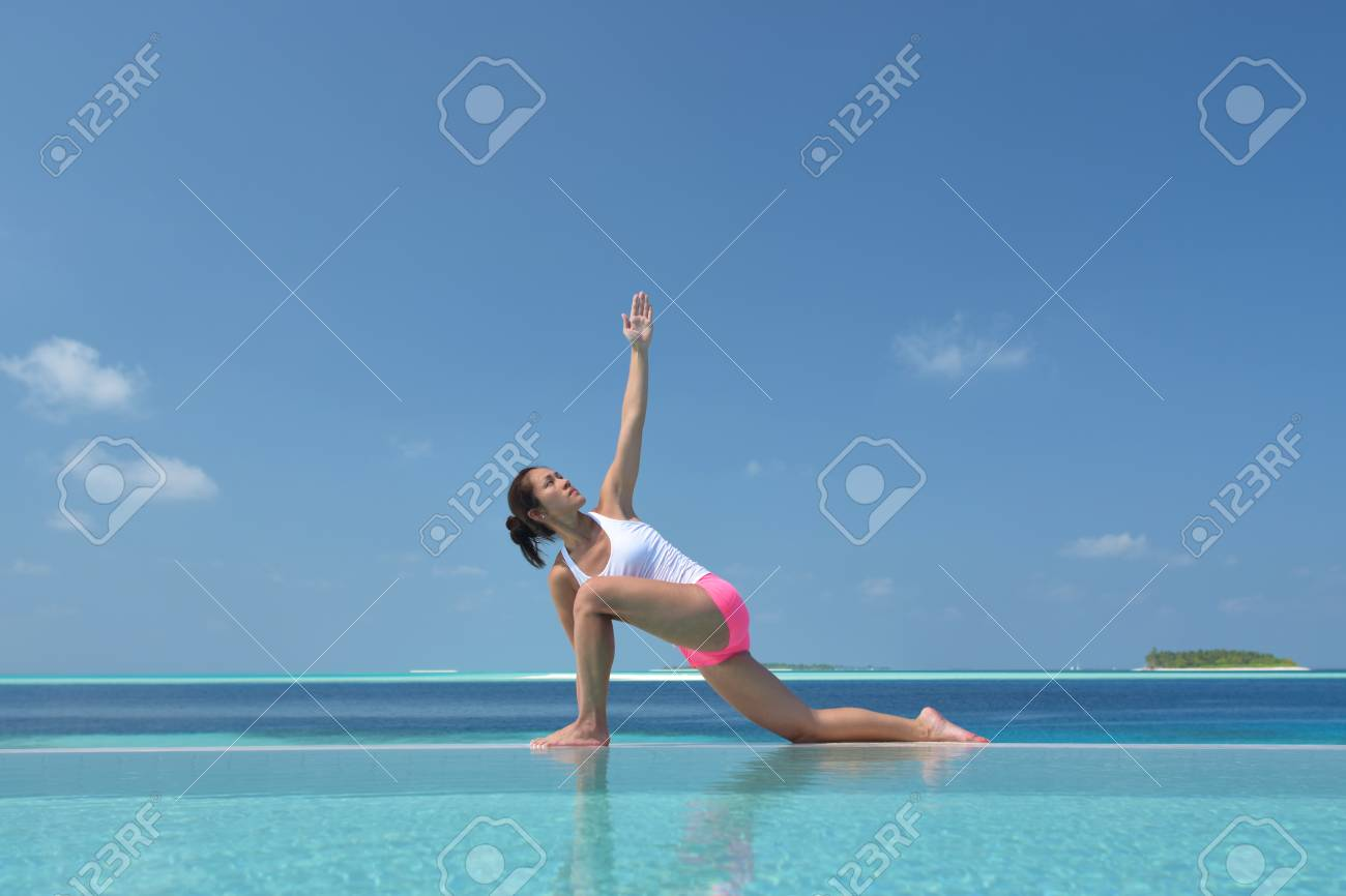Asian chinese woman in yoga pose by the sea - 33319860
