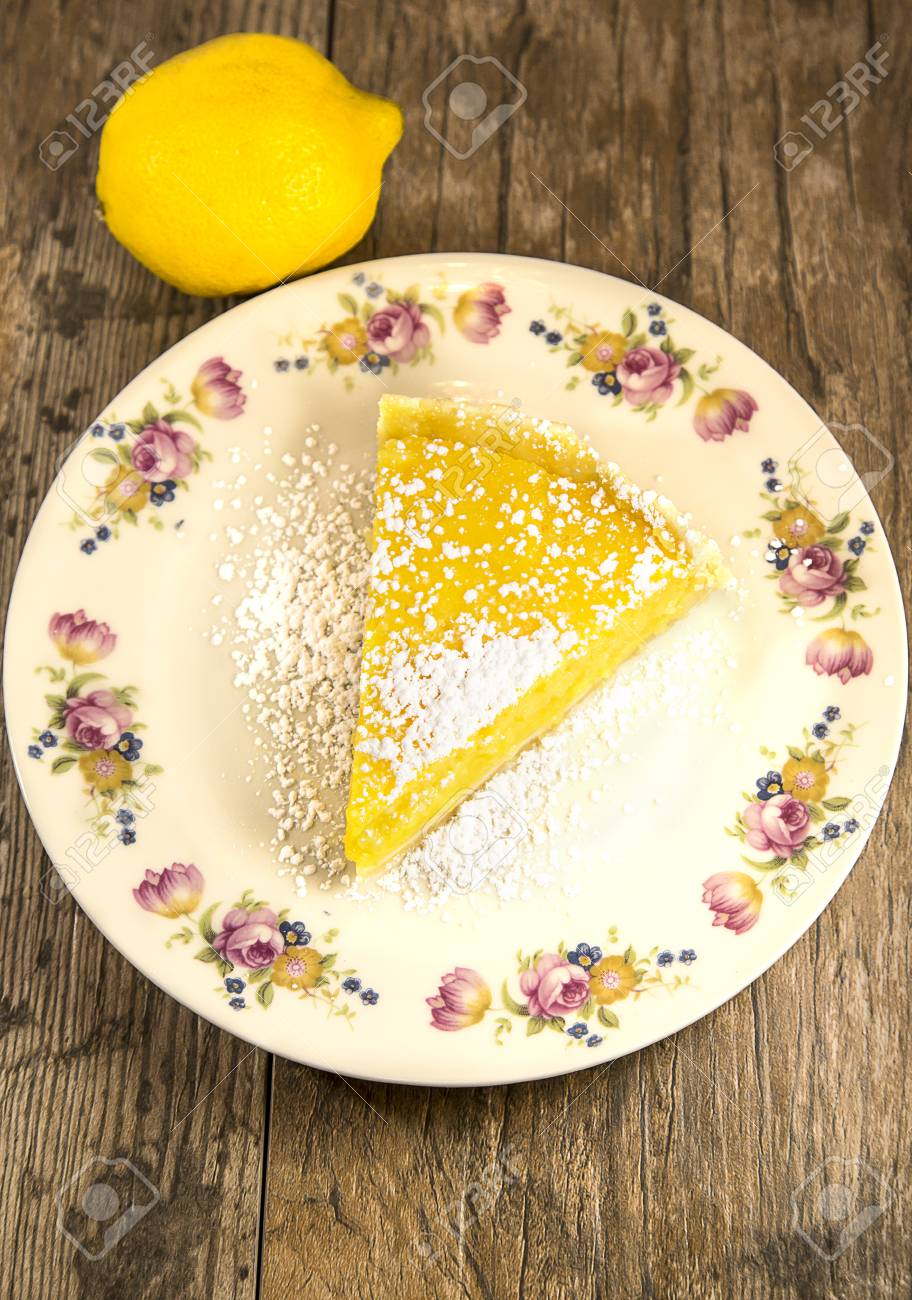 Lemon Tart slice on old fashioned plate, isolated on a wooden table Stock Photo - 83522439