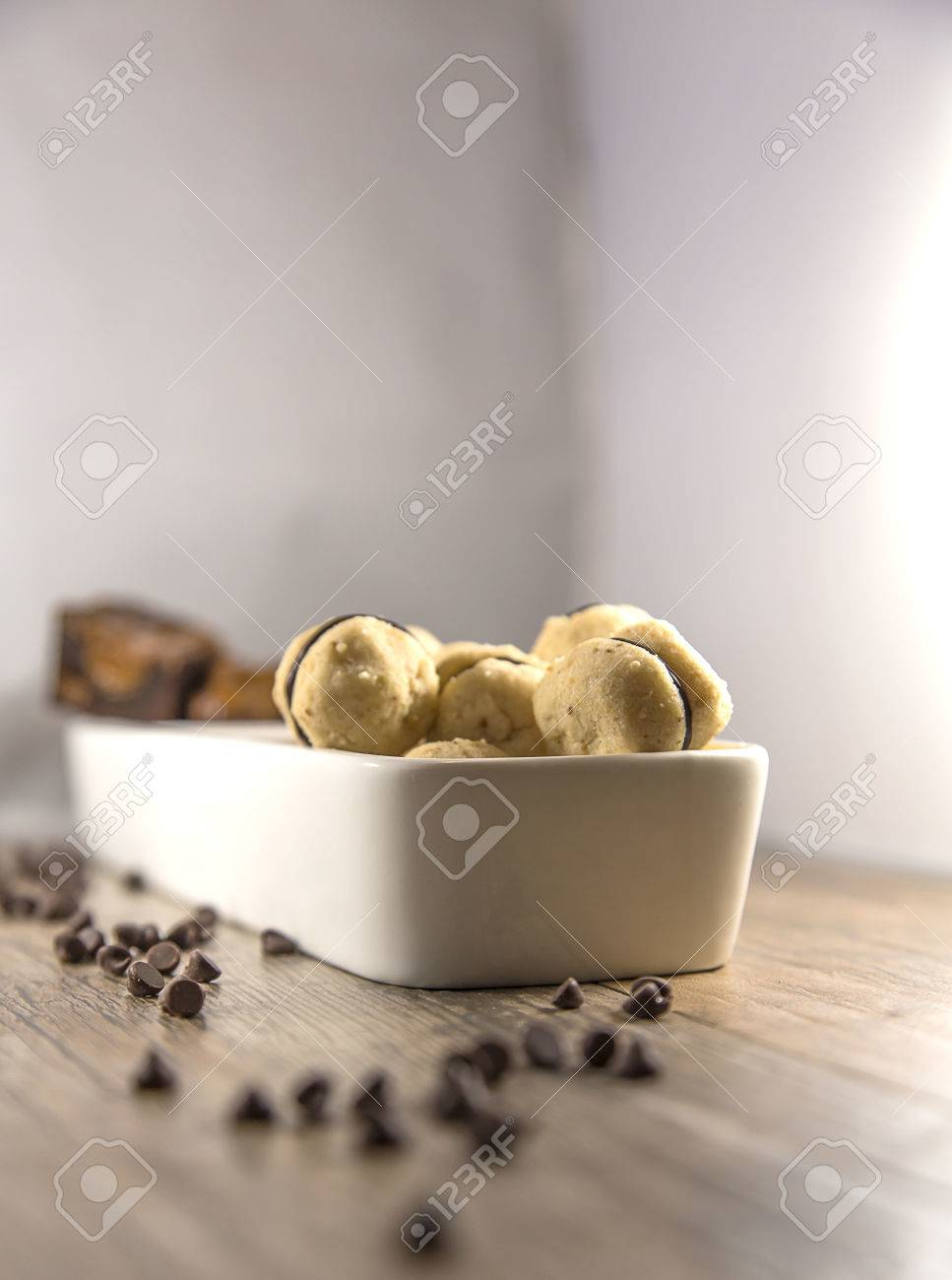 Display of round mini hazelnut cookies displayed in a white serving dish, with chocolate chips Stock Photo - 83522442