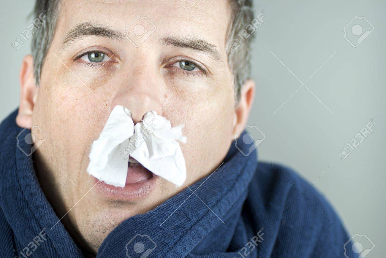 Close-up of a man with tissue in his nose. - 9196911