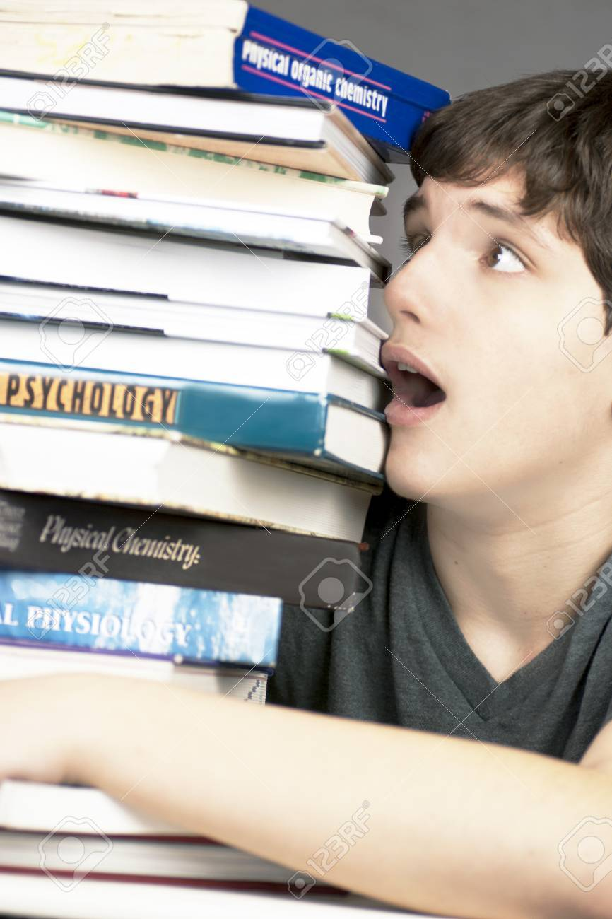 Close-up of a terrified teen looking at a stack of textbooks. - 9328627