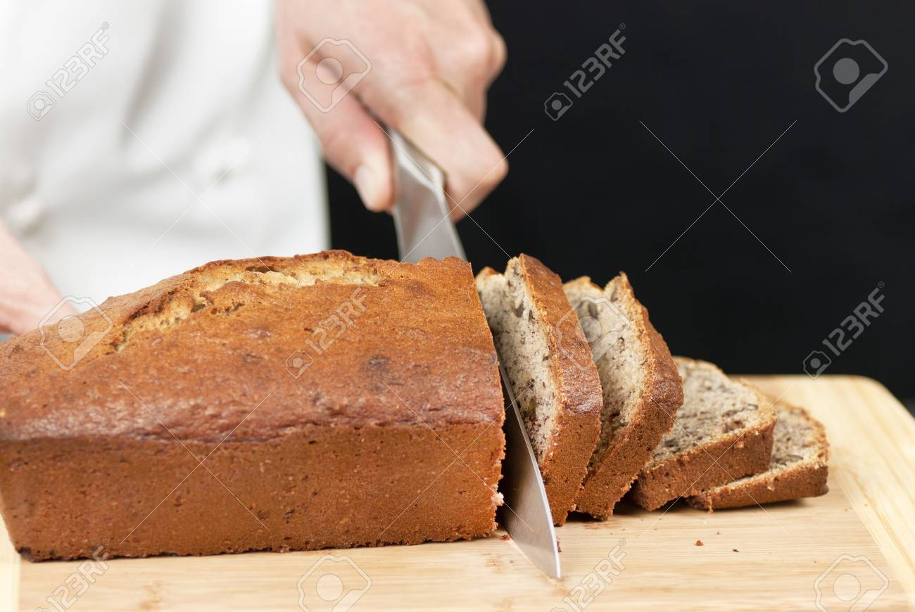 Close-up of a chef slicing banana bread on a bamboo cutting board. - 9585267