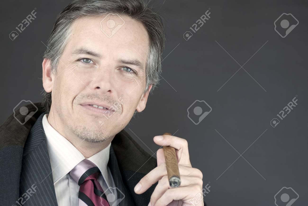 Close-up of a successful businessman holding a cigar. - 9806928