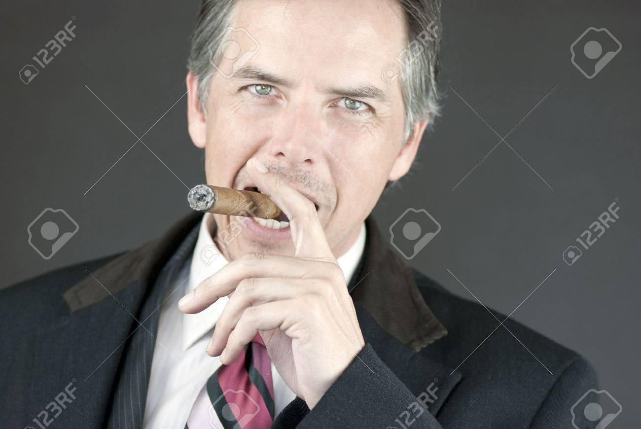 Close-up of a confident businessman smoking a cigar. - 9806927