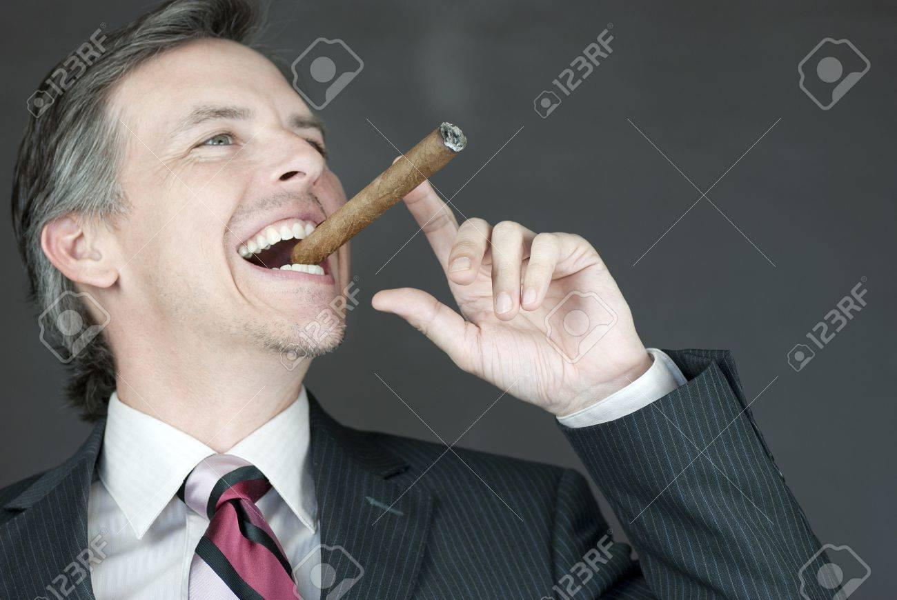 Close-up of a businessman celebrating with a cigar, side view. - 9806921