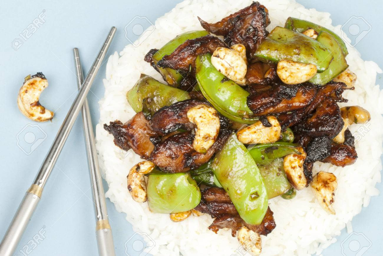 Close-up of chicken cashew on rice with stainless steel chopsticks. Stock Photo - 10376342