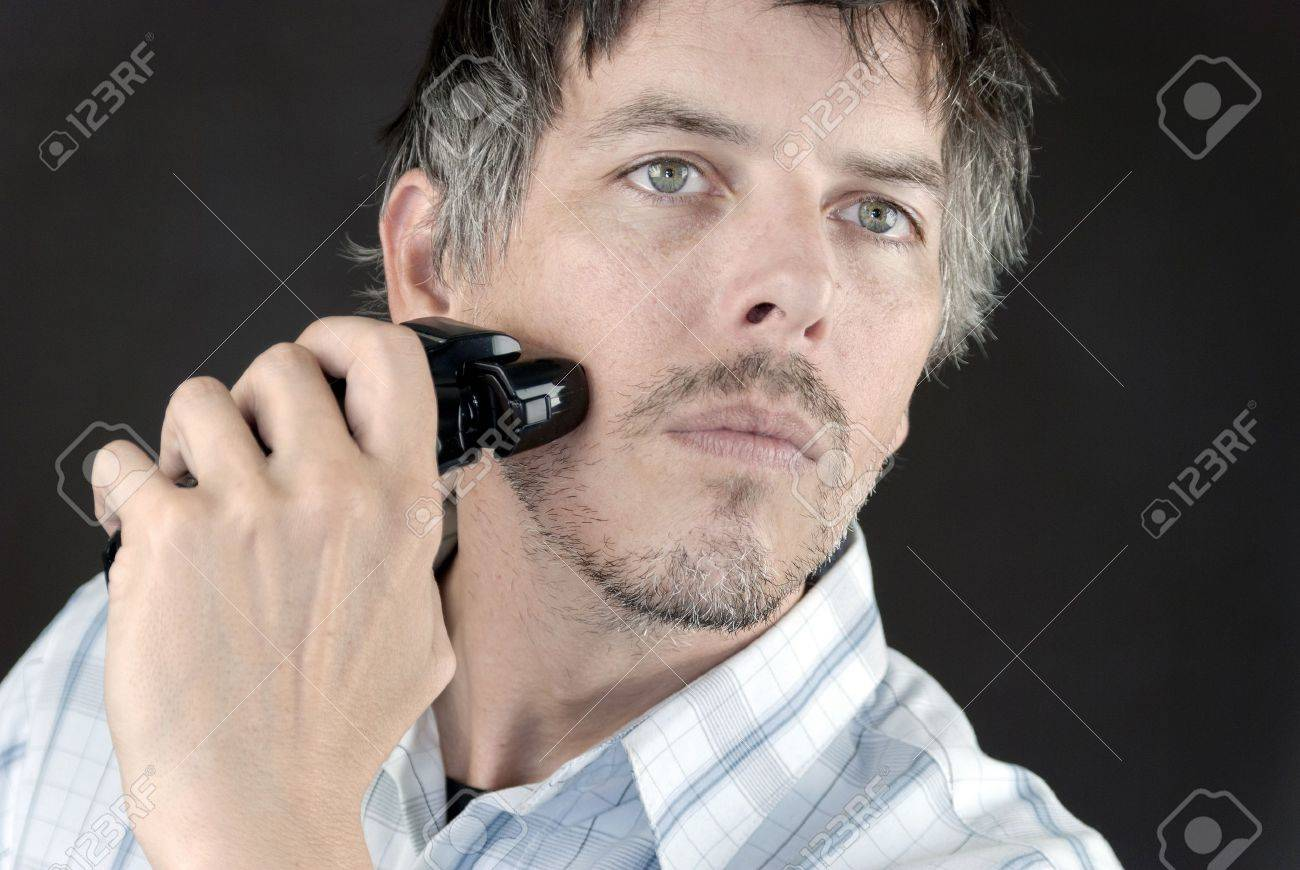 Close-up of a man using an electric razor to shave. - 11369386