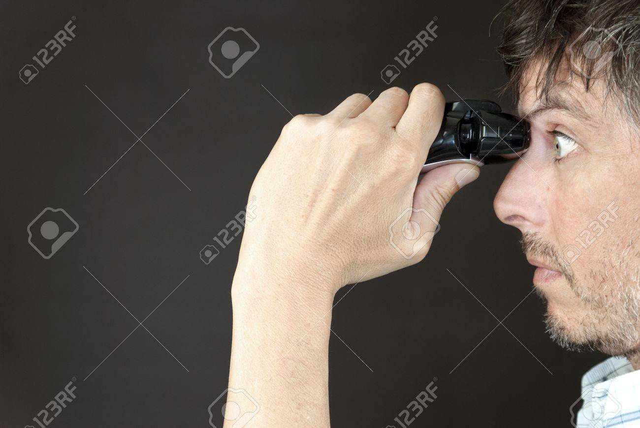 Close-up of a man trimming his monobrow with a full sized electric razor. - 11369380