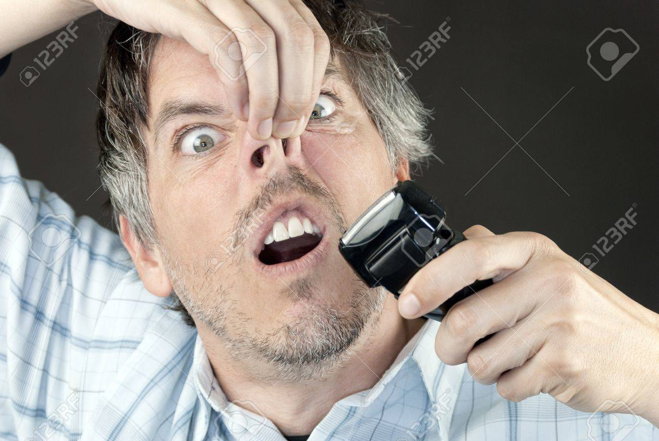 Cloe-up of a man attempting to trim his nose hair with a full sized electric razor. - 11369425