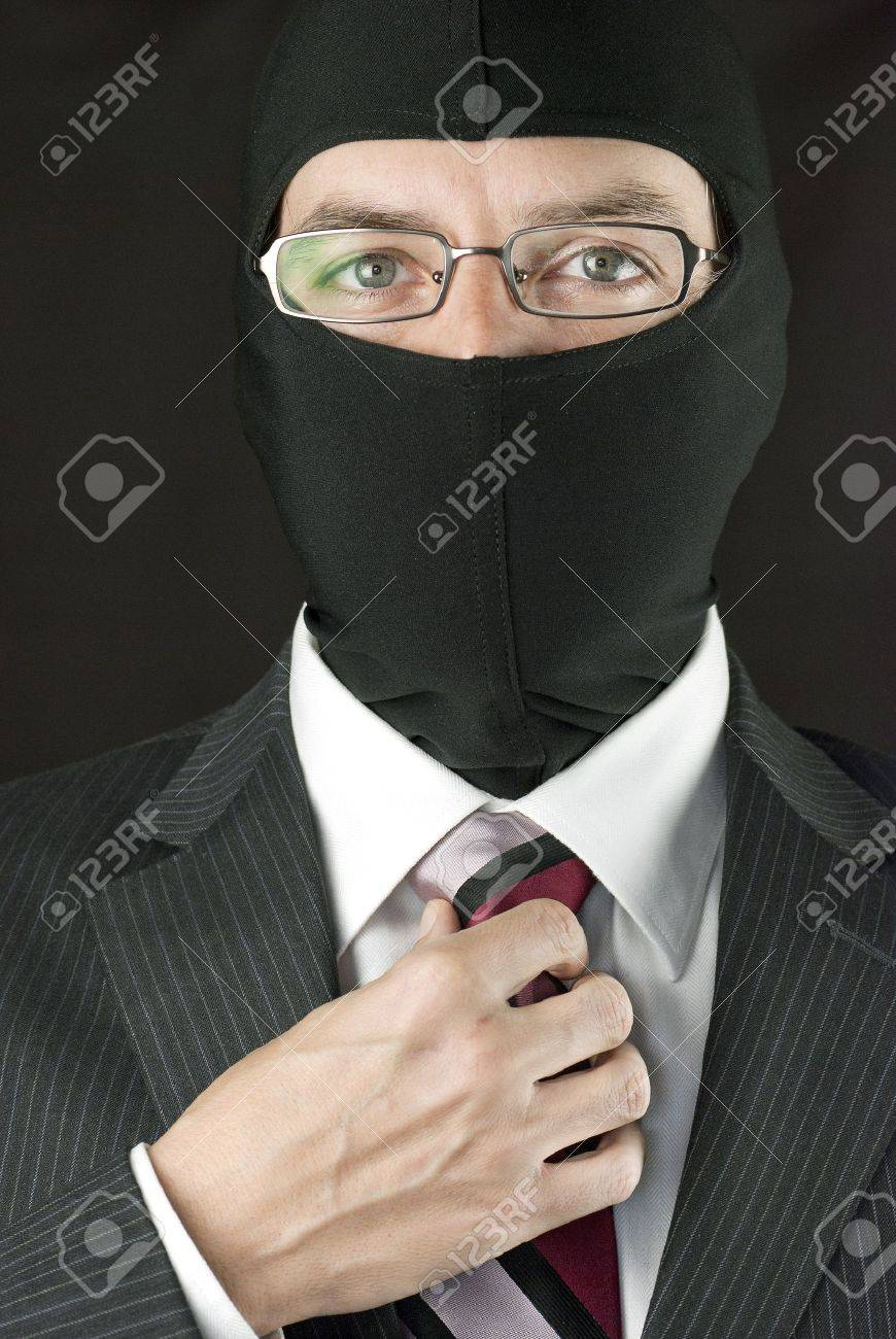 Close-up of a businessman wearing a balaclava adjusting his tie. - 11369432