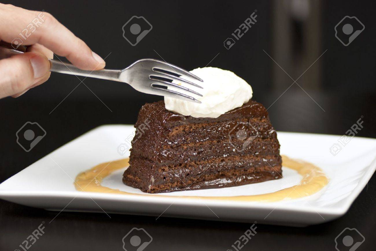 Close-up of a hand holding a fork about to slice into a chocolate marquise with a white chocolate marscapone and butterscotch sauce. - 11369444