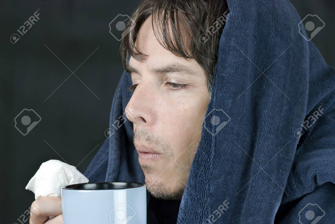 Close-up of a sick man holding a tissue blowing on a hot mug. - 11369419