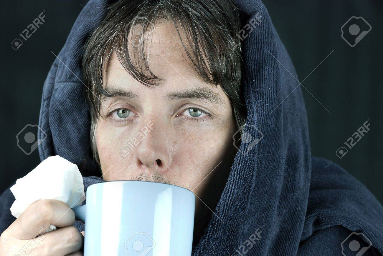 Close-up of a sick man holding a tissue drinking from a hot mug. - 11369420