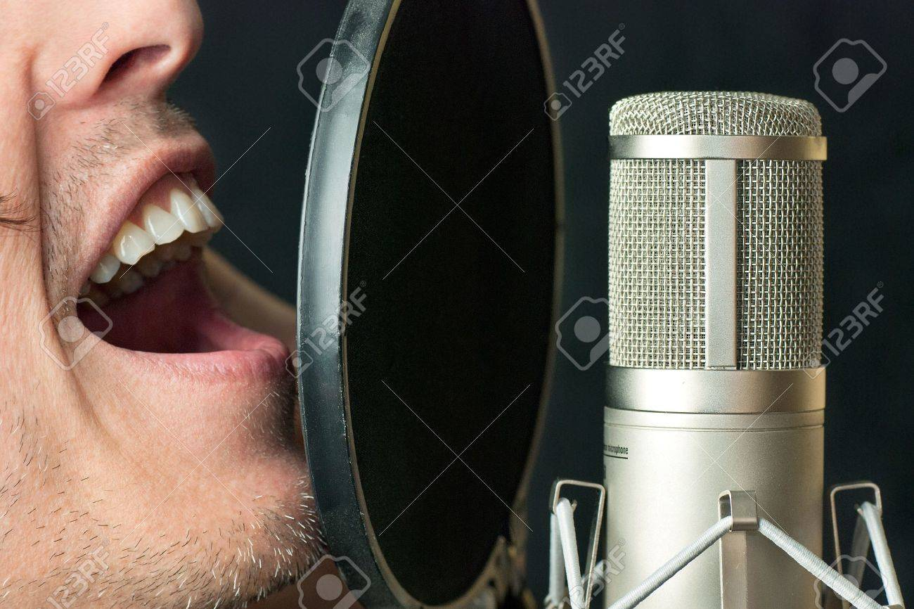 Super close-up of a man singing into a condenser microphone Stock Photo - 14900649