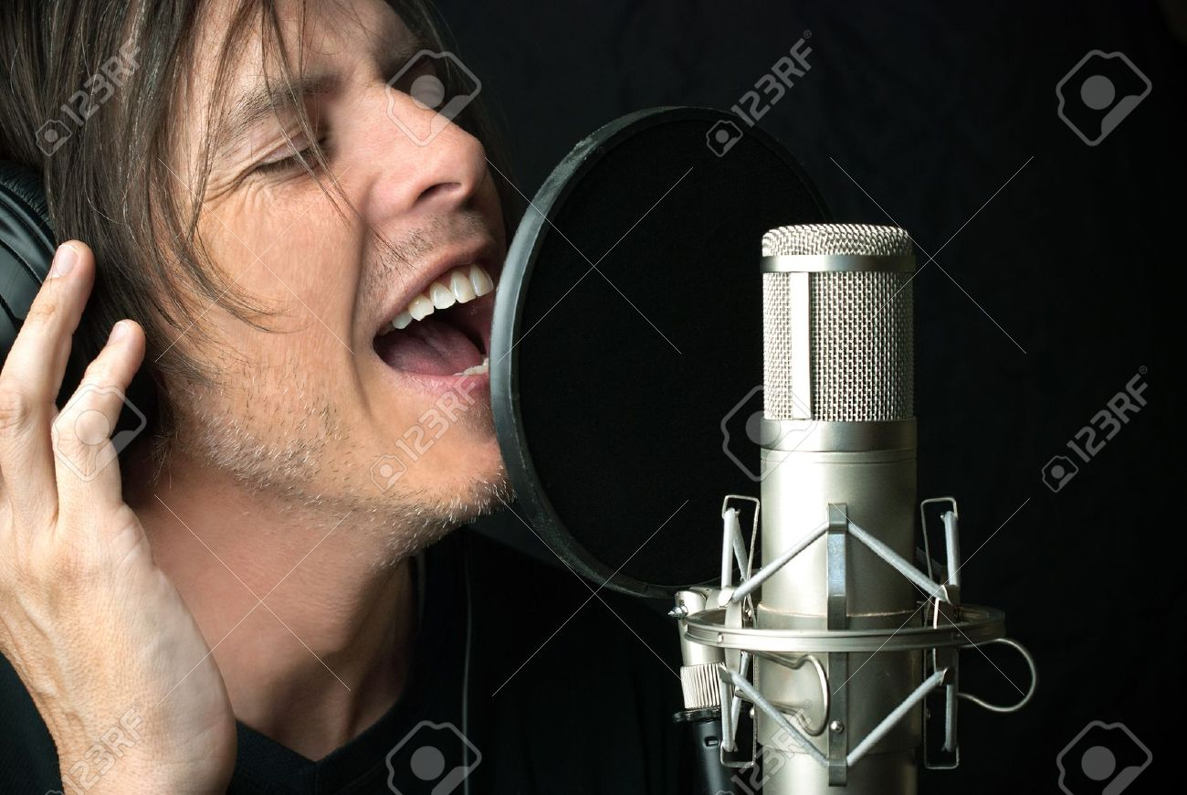 Close-up of a man singing into a condenser microphone. Stock Photo - 14900645