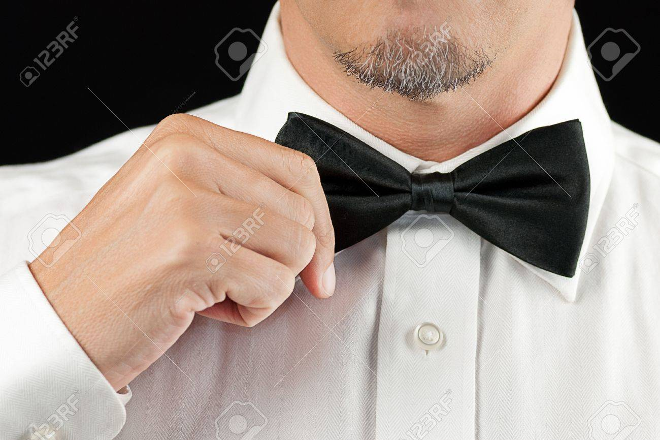 Close-up of a man in a tux straightening his bowtie, one hand, no jacket - 15832245