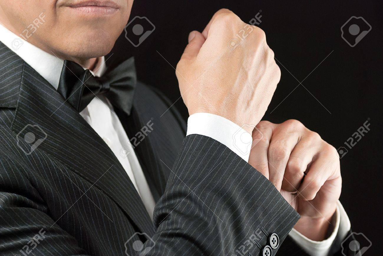 Close-up of a man in a tux fixing his cufflink - 15832249