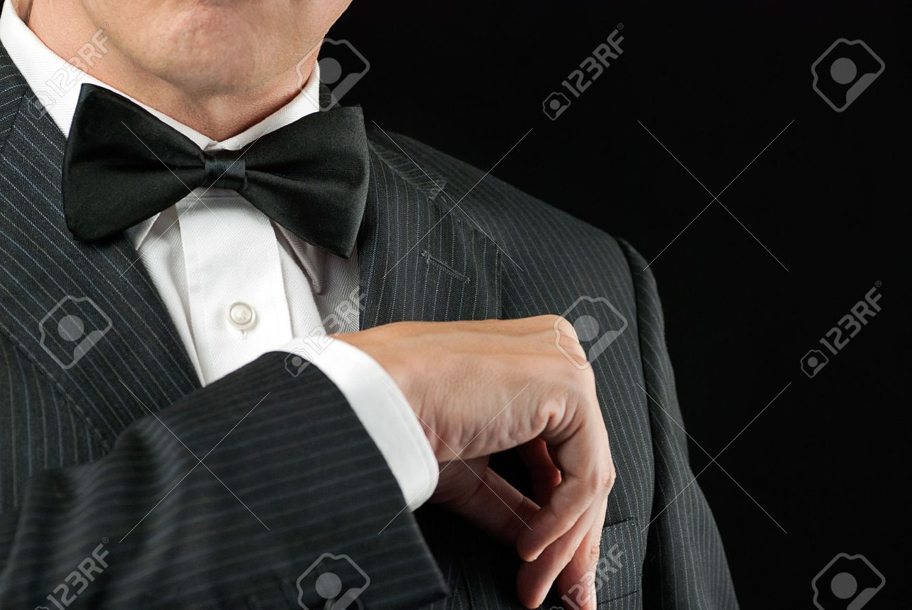 Close-up of a man in a tux tucking in his pocket square - 15832247